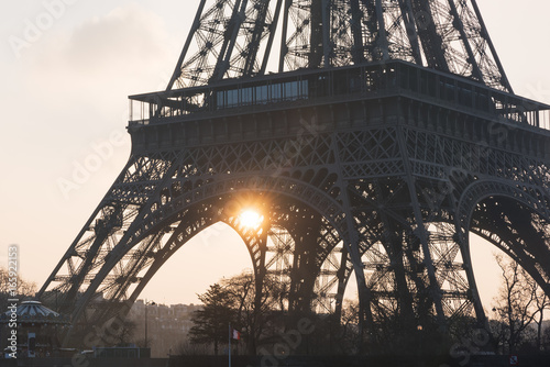 Eiffel tower close-up against sun at sunrise - Paris