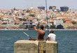 Two men fishing in river Tagus - Lisbon's cityscape in the background