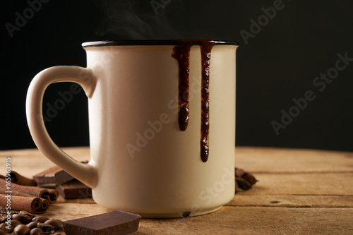 Spoed canvasdoek 2cm dik Chocolade Mug of hot chocolate drink and chocolate pieces, cinnamon sticks, coffee beans on wooden rustic table isolated on black background. Closeup