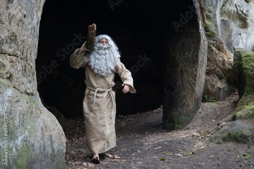 The bearded monk carries log. The old hermit working in a cave. Poster