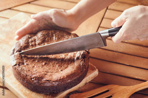 Hand holding knife and cutting chocolate brownie cake