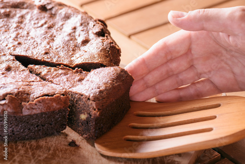 Hand taking piece of delicious chocolate cake with walnuts