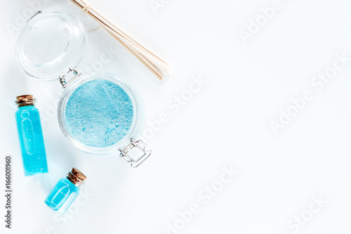 Spa set with sea salt, blue clay and lotion on white background top view copyspace