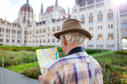 Foto Murales Senior tourist man in hat searching for destination on map