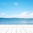 Empty perspective white wood over blur blue sea and sky background, nature background, spring and summer, tropical climate, travel concept, for product display montage