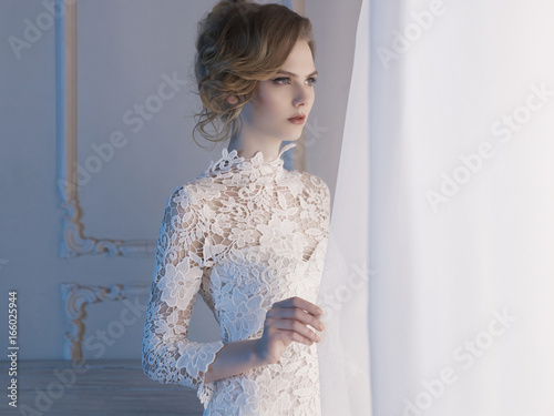 Woman in lace dress at the window