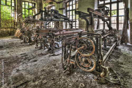 Poster Oude verlaten gebouwen Old weaving looms and spinning machinery at an abandoned factory