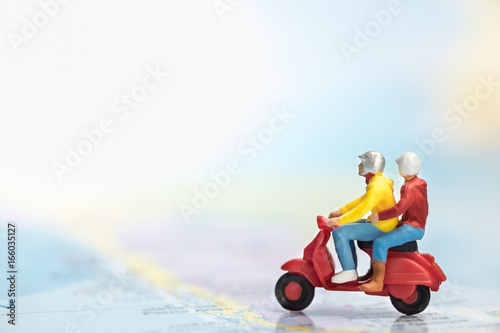 Aluminium Scooter Travel Concept. Group of traveler miniature figures ride motorcycle / scooter on world map.