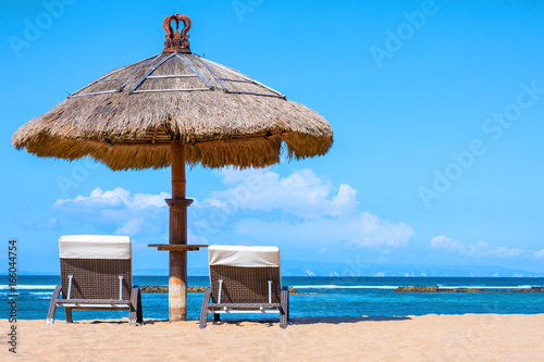 A thatched roof shady umbrella with lounge chairs on the sand overlooking a tropical beach on a prefect day.