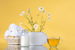 Quadro Chamomile flowers stand in a white vase. A cup of herbal tea. Three white towels rolled into a roll lie in a basket. Jar with cream. The background is yellow. Still life