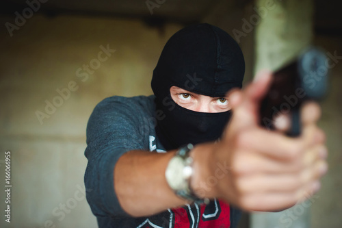Athletic man in a balaclava, holds a pistol in his hand, is threatened with shoo Poster
