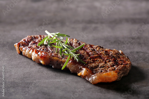 Grilled beef steak on stone board with spices