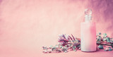 Natural cosmetic product in bottle with herbs and flowers on pink background, front view, banner, place for text. Healthy skin or body care or beauty , wellness treatments concept - 166077539