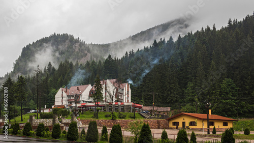 Mountains scenery, residential building in mountains, rocks and forest at clouds, rain weather, Carpathians, Romania