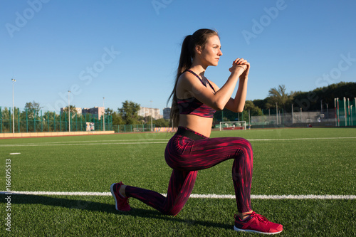 Young happy sportswoman in sportswear making lunges exercise on stadium field area outdoors. Healthy lifestyle concept, sport activity.