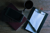 home desk table with smartphone, pen on notebook,  cup of coffee. Top view ,vintage style(selective focus)