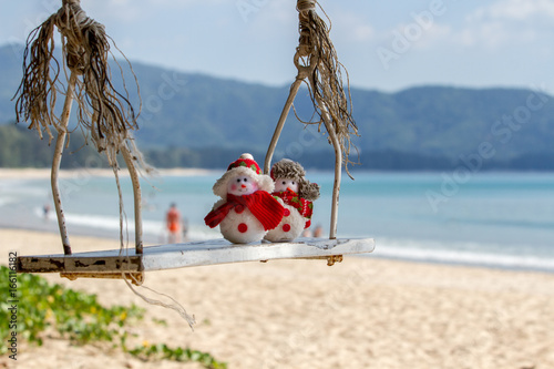 Two snowman swinging on a swing in a warm Paradise Poster