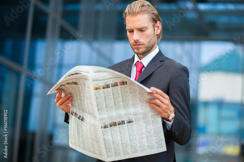 Manager reading a newspaper outdoor