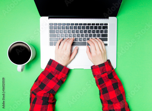 Leinwandbild Motiv Freelancer woman hands with cup of coffee and laptop