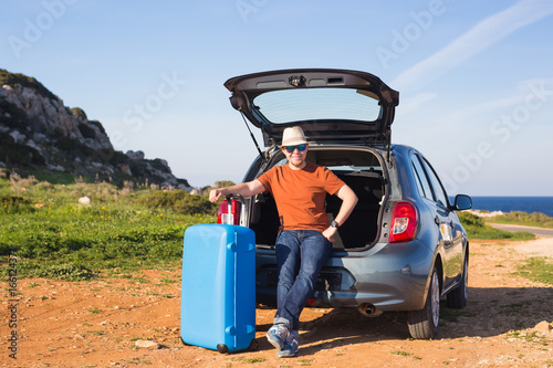 Funny happy man going on summer vacation. Car travel concept