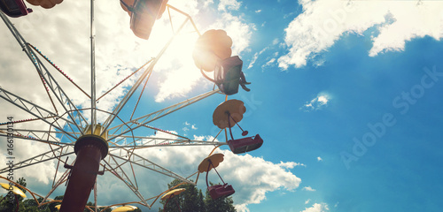 amusement park carousel against blue sky with copy space