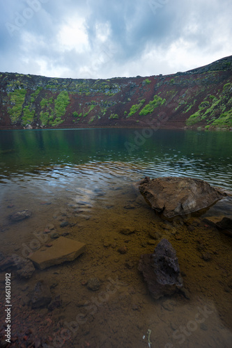 Iceland - Stones in clear blue water at Kerid Crater Lake