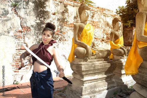 Foto op Plexiglas Draken Pretty Asian woman posing in Thai ancient warriors at Wat Phutthaisawan temple in Ayutthaya Historical Park ,Thailand.
