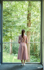 woman looking into the window green forest