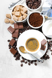 cup of espresso, ingredients and sweets on white background, vertical, top view