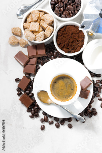 Sticker cup of espresso, ingredients and sweets on white background, vertical, top view