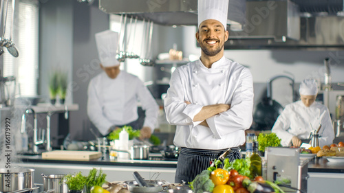 Famous Chef of a Big Restaurant Crosses Arms and Smiles in a Modern Kitchen. His Staff in Working in the Background. - 166179922