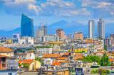 Panorama miasta Mediolanu z dachu budynku, w daleko w kraju grzbiet górski jest widoczny