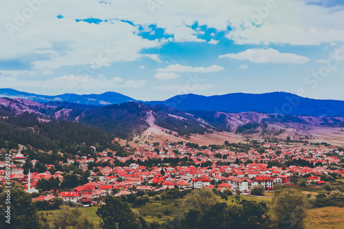 Photo depicting a beautiful colorful amazing mountain meadow paradise landscape, summertime. European alpine mountains in sunshine on a blue sky background.