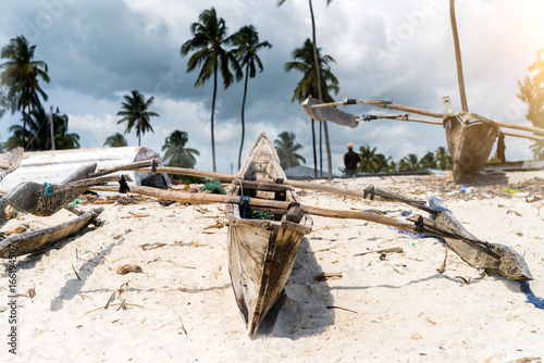 old wooden fishing boat with paddles on a beach of fishing village in Zanzibar