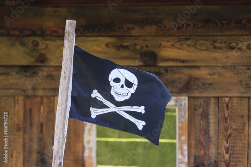 The pirates flag / the jolly roger waving against  background of a wooden boards Poster
