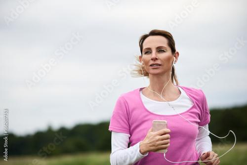 Ehrgeizige schlanke Frau trainiert in der Natur