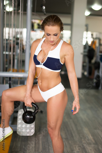Young fit woman workout with kettlebell in gym