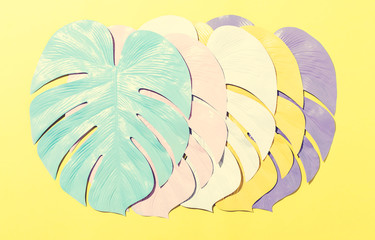 Painted tropical monstera leaves with hard shadow on a yellow background