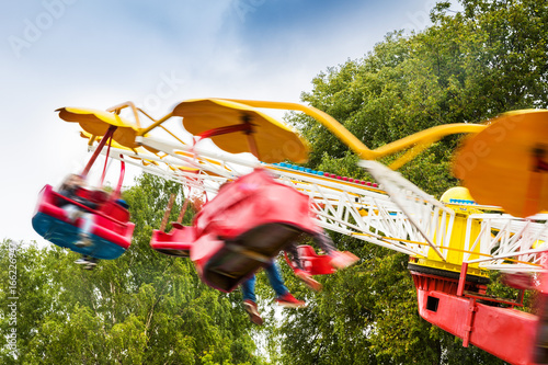 people having fun in amusement park carousel. motion blur