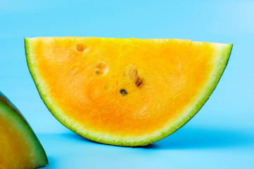 Yellow watermelon slice against blue background