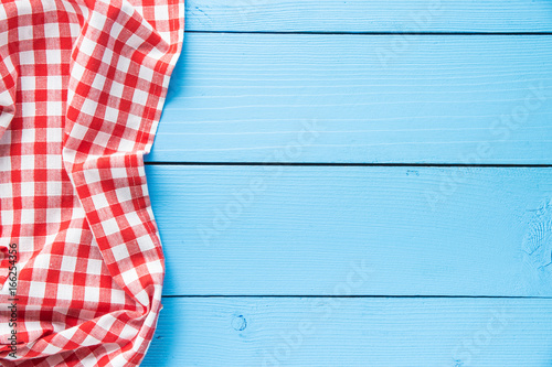 Checkered tablecloth over colorful wooden table.