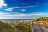 Wooden staircase and blue sky among dunes and high grass on North Sea coast in Belgium