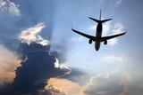 passenger plane flies in juicy clouds to meet the sun.