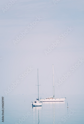 Sailing yacht in the blue sea with sails down, summer landscape