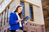Girl checks her tablet standing on the street