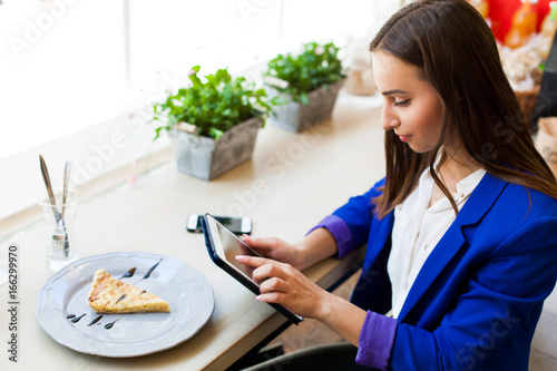 Girl in a cafe reads something on the tablet