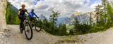 Mountain biking couple with bikes on track, Cortina d'Ampezzo, Dolomites, Italy - 166300779