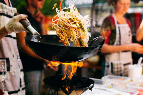 Man cooks noodles on the fire - 166300926