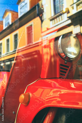 Red motor scooter in the city reflection