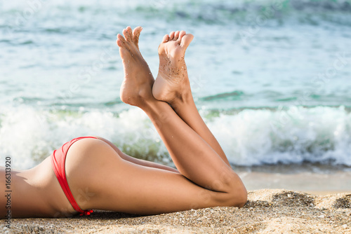 Tanned legs and seductive buttocks on the beach sand near the sea
